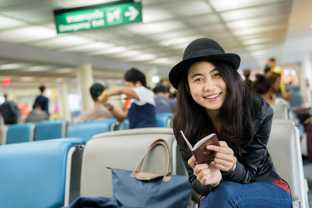 Asian student at the airport with passport