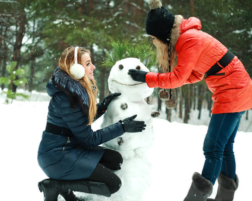 students building a snowman in Christmas